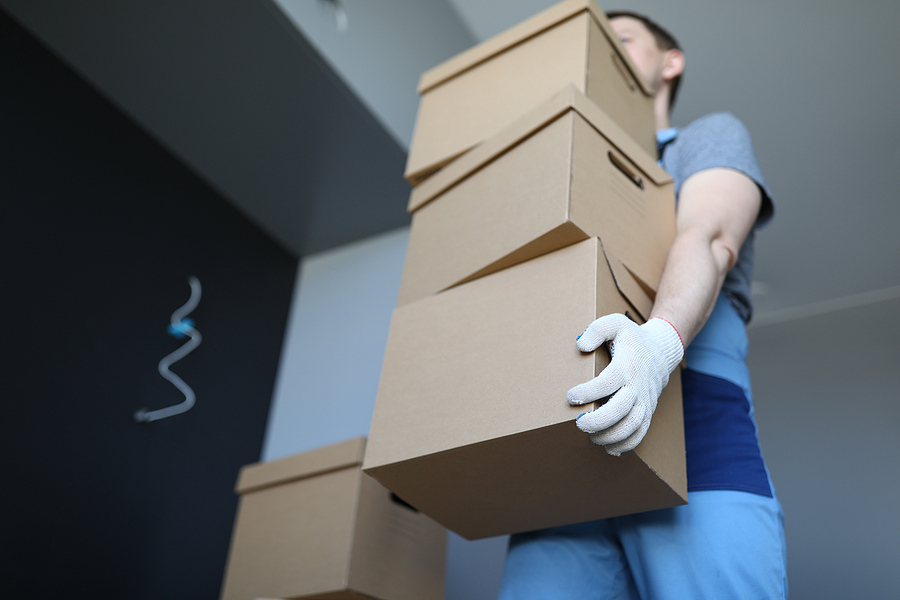 Removalist carrying pile of boxes