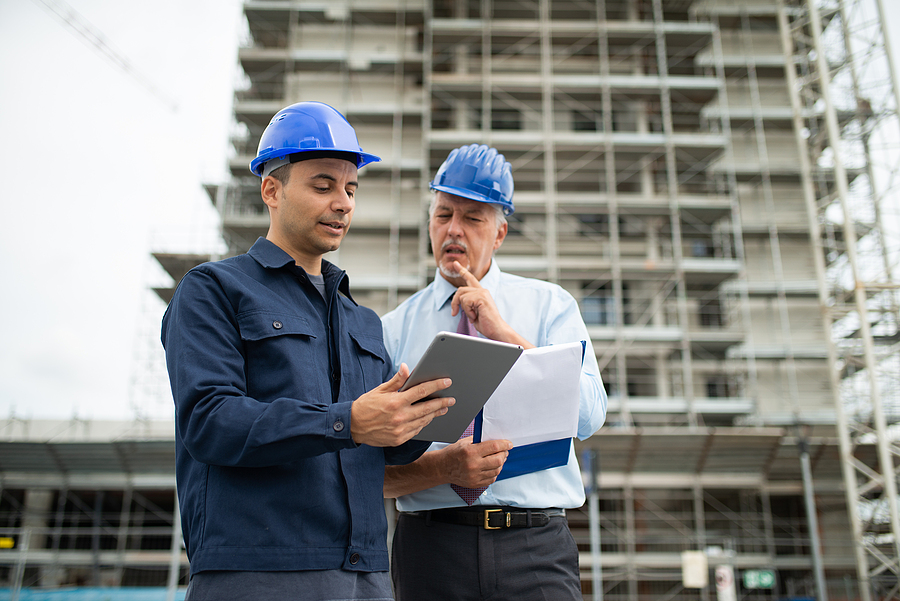 Architect and site manager using a construction project management software installed in a tablet