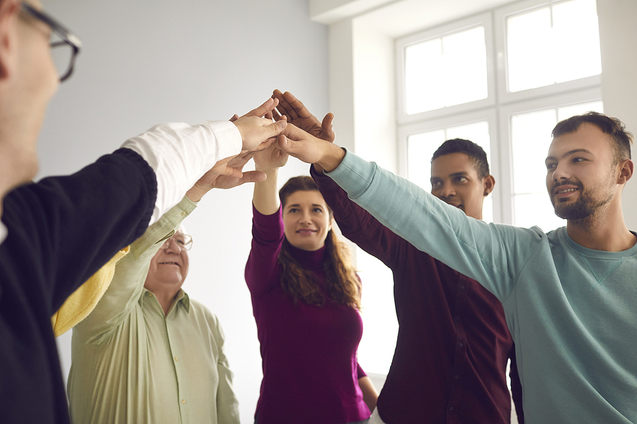 Team of happy diverse people joining hands during team building events
